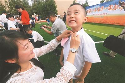 城小学南校区为一年级新生举办入学仪式,家长给孩子扣第一粒扣子
